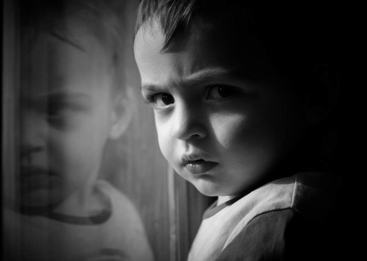 Four-year old boy stares intently out the window.