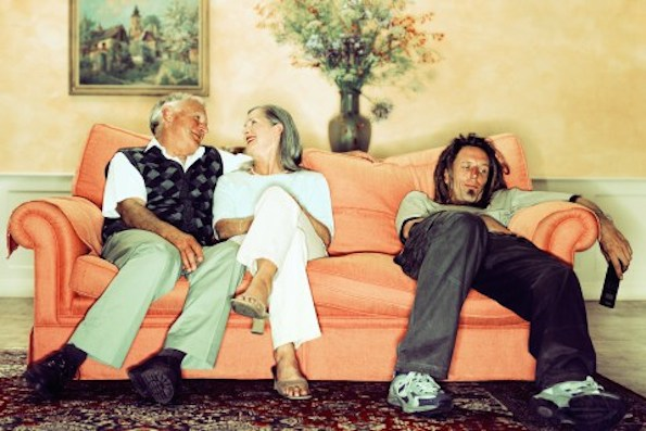 Millennial sits on couch next to his baby boomer parents.