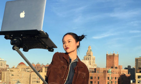 Millennial student uses macbook selfie stick to take a picture of herself.