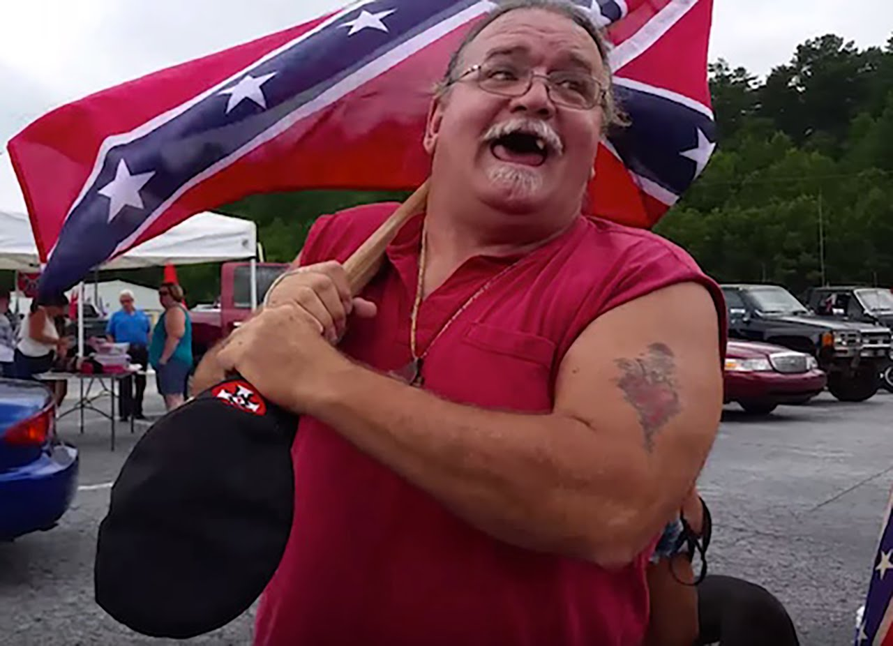 Toothless redneck waves confederate flag in the air at a White Power rally.