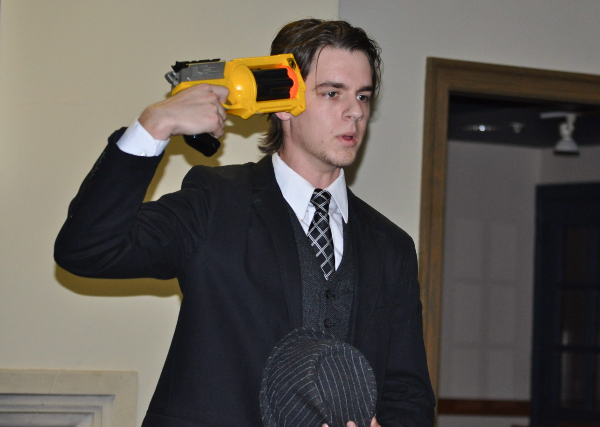 Slam poet holds nerf gun up to head during a performance.